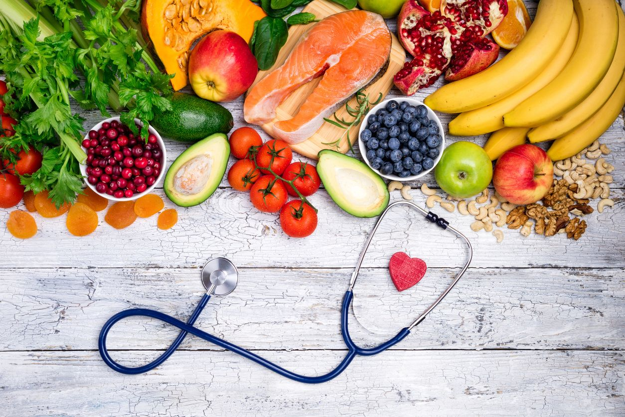 A stethoscope sitting in front of a pile of healthy fruits and veggies health insurance