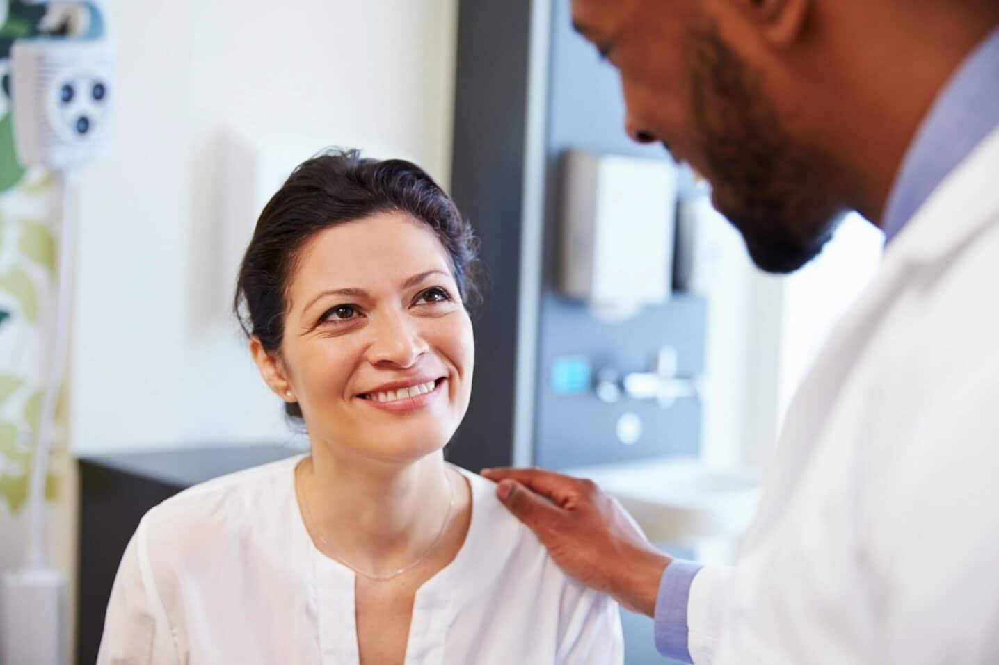 A male doctor is consoling a female patient about insurance in a doctor's office