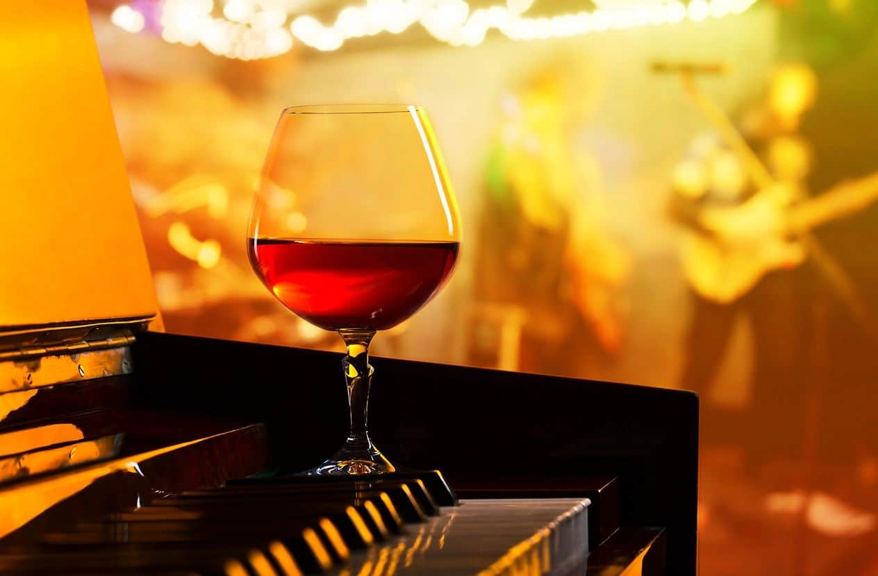 A glass of red wine on a table with a band in the background
