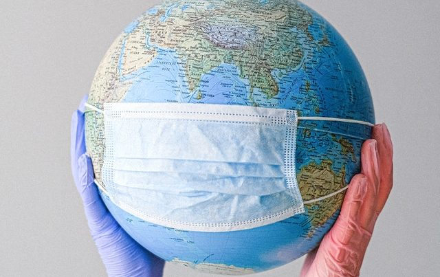 Globe wearing mask with gloved hands holding it up, trash